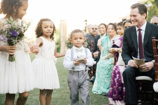 wedding-party-flower-girls-in-white-dresses-bouquets-purple-ring-bearer-in-grey-pants-suspenders