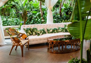 tropical-leaf-print-throw-pillows-on-tufted-sofa-rose-gold-coffee-table-armchair-at-wedding-lounge