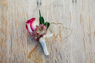red-white-and-purple-boutonniere-with-rose-and-leaves-sits-on-top-of-wooden-table-with-hearts-carved