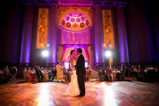 bride-and-groom-share-their-first-dance-in-the-andrew-w-mellon-auditorium-at-a-purple-gold-wedding