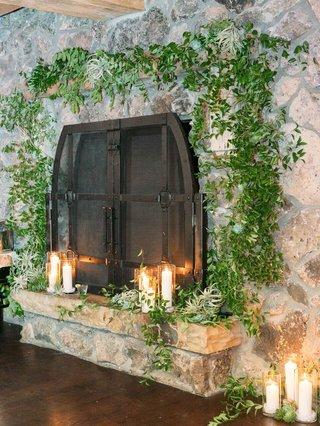 stone-fireplace-surrounded-by-greenery-and-with-candles