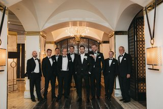 groom-in-white-tie-and-tuxedo-groomsmen-in-black-ties-and-tuxedos