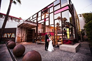 bride-and-groom-in-front-of-hotel-maya-courtyard-with-glass-building-in-long-beach