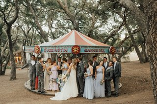 mixed-gender-wedding-party-with-bride-and-groom-on-carousel-at-saddlerock-ranch