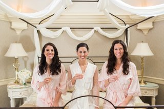 bridal-suite-decorated-with-white-sheets-white-bridal-robe-and-pink-bridesmaid-robes-champagne