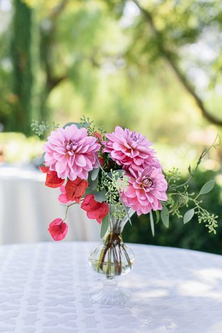 a-small-floral-arrangement-of-flowers-in-different-shades-of-pink-and-foliage-in-small-vase