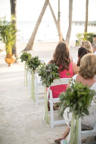 wedding-guests-sitting-on-white-foldable-chairs-beach-ceremony-greenery-on-ends-of-chairs