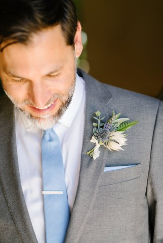 groom-in-grey-suit-and-light-blue-tie-wildflower-boutonniere