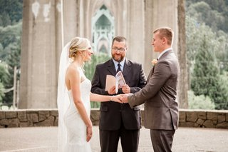 couple-exchanging-vows-portland-oregon-park-wedding-outdoors-officiant-reading-book-veil-rustic