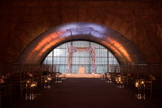 dimly-lit-ceremony-space-featuring-a-white-chuppah-and-stage-with-cherry-blossoms