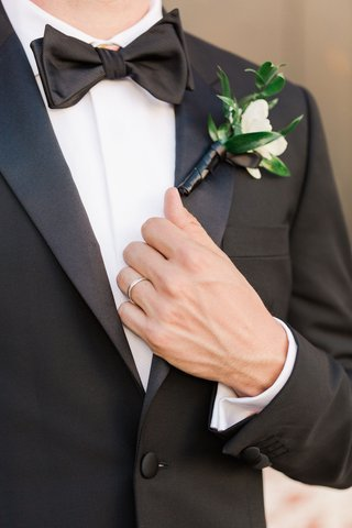 groom-in-suit-and-bow-tie-holding-lapel-silver-platinum-wedding-ring-greenery-boutonniere-white