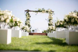wooden-chuppah-white-green-florals-seaside-ceremony-arrangements-down-aisle-jewish-wedding