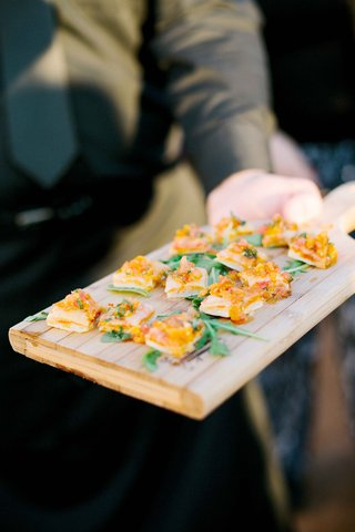 beachside-cocktail-hour-with-server-passing-crostini-appetizers-on-wood-cutting-board