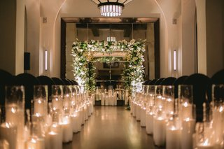 wedding-ceremony-hotel-figueroa-candles-along-aisle-black-guest-chairs-greenery-white-flower-chuppah