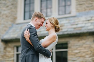 blonde-bride-with-low-chignon-bun-hugs-groom-in-grey-suit