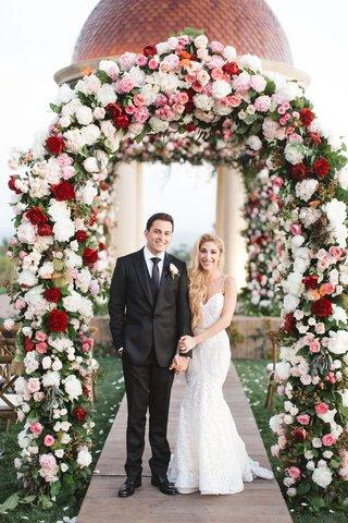 newlyweds-underneath-colorful-floral-arch-pelican-hill-resort-wedding-newport-beach-california-berta