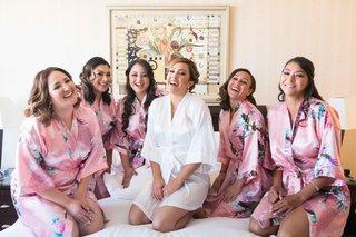 bride-bridesmaids-laughing-pink-robes-white-flower-getting-ready-silk-hair-makeup-california-wedding