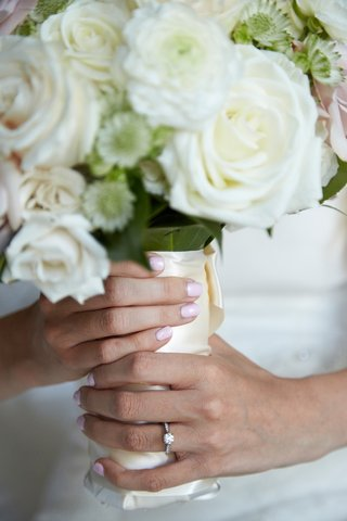 bride-with-solitaire-engagement-ring-and-baby-pink-bridal-nails-holding-white-bouquet
