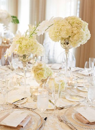round-wedding-table-with-rosette-linen-mercury-glass-vessels-with-hydrangea-and-orchid-flowers