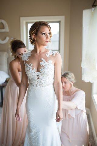 bride-in-pronovias-gown-with-illusion-neckline-lace-bodice-bridesmaids-help-bride-into-dress