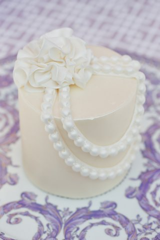 personal-white-wedding-cake-with-sugar-flower-and-string-of-pearls-on-versace-plate