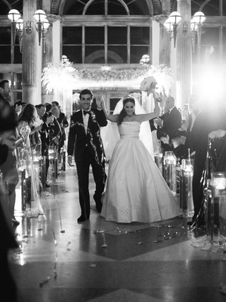 black-and-white-photo-of-bride-and-groom-walking-up-aisle-as-husband-and-wife-confetti-explosion