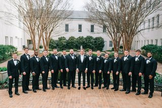 large-wedding-party-groomsmen-in-suits-and-bow-ties-on-brick-flooring-groom-in-center-with-white-tie