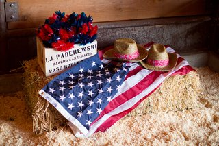 wooden-box-of-blue-and-red-pinwheels-on-top-of-hay-bale-with-american-flag-and-cowboy-hats