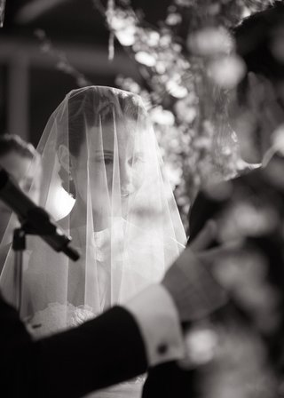 black-and-white-picture-of-a-bride-with-her-blusher-over-her-face-during-the-ceremony