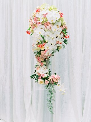 tall-ceremony-floral-arrangement-white-orchids-blush-flowers-leafy-greenery-white-backdrop