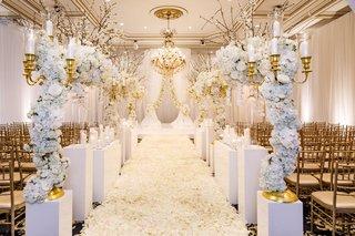 ballroom-wedding-gold-chairs-white-flower-petal-aisle-white-riser-gold-candelabra-flower-branches