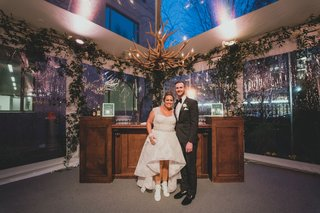 bride-in-second-wedding-dress-high-low-gown-in-front-of-mahogany-cocktail-hour-bar-antler-chandelier