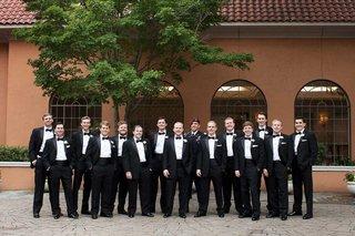 groom-with-groomsmen-in-tuxedos-and-one-groomsman-in-uniform