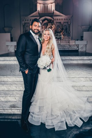 bride-in-lazaro-mermaid-wedding-dress-long-blonde-hair-veil-white-bouquet-with-groom-in-suit-white