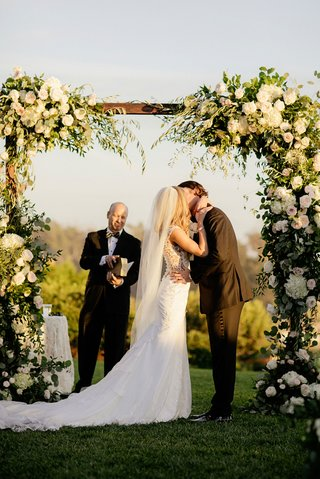 amy-crawford-and-gerrit-cole-white-veil-under-arbor-with-greenery-and-white-flowers-gerrit-cole