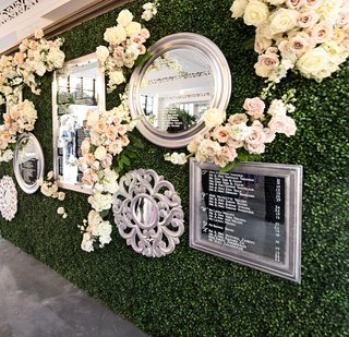 wedding-reception-green-hedge-wall-flowers-mirrors-with-seating-assignments-seating-chart-display