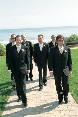 men-in-black-tuxedos-walking-away-from-beach