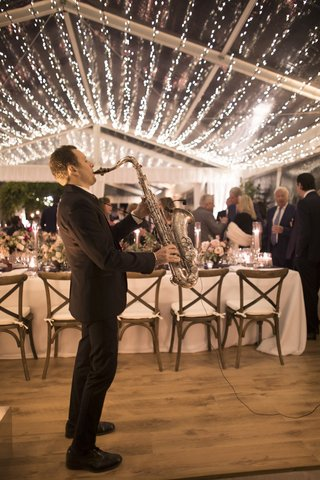 man-in-black-suit-playing-saxophone-during-tented-reception-with-twinkle-lights-covering-ceiling