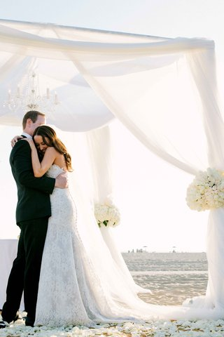 bride-in-a-strapless-alencon-lace-dress-hugs-groom-in-black-tuxedo-under-white-beach-ceremony-canopy