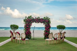 wedding-ceremony-at-acqualina-resort-and-spa-in-florida-greenery-arch-pink-flowers-chairs-garlands
