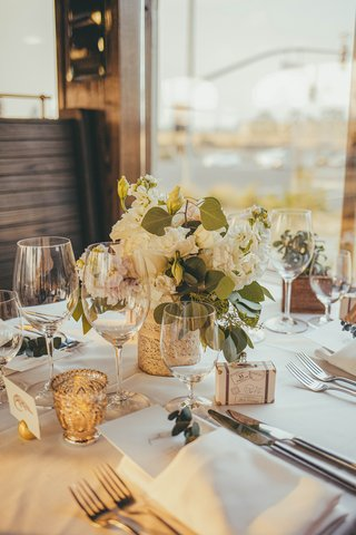 wedding-reception-on-train-car-table-with-small-floral-arrangement-and-detailed-gold-votive