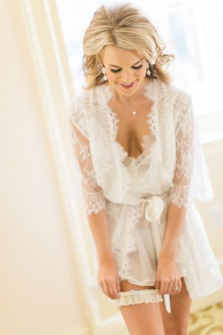 bride-slips-on-lace-garter-while-wearing-sheer-lace-robe-before-wedding-ceremony-blonde