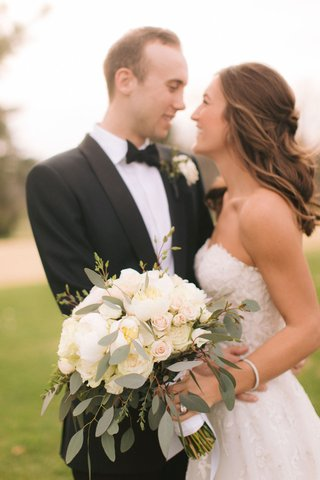 groom-in-tuxedo-bow-tie-bride-in-strapless-reem-acra-wedding-dress-ivory-bouquet-half-up-half-down