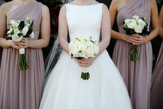 bride-in-bateau-neckline-wedding-dress-white-rose-bouquet-bridesmaids-mauve-dresses-white-greenery