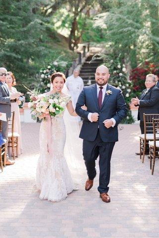 bride-in-pretty-wedding-dress-groom-in-navy-suit-and-burgundy-tie-dress-shoes-brick-floor-outdoor