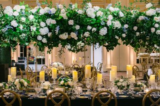 wedding-reception-long-table-gold-chairs-candles-tall-centerpiece-white-rose-hydrangea-blue-flowers