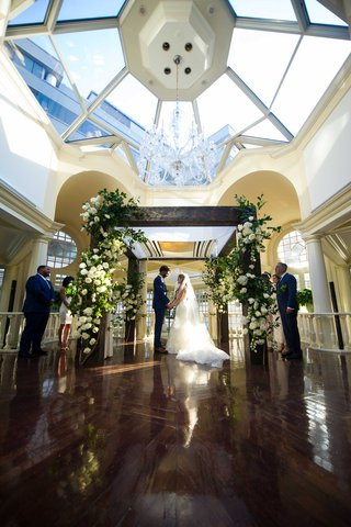 a-couple-weds-in-traditional-jewish-ceremony-under-wooden-chuppah-with-white-florals-and-greenery