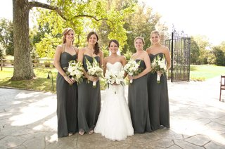 bride-and-bridesmaids-in-gray-dresses-with-bouquets-of-white-lilies-flowers-and-green-leaves-foliage