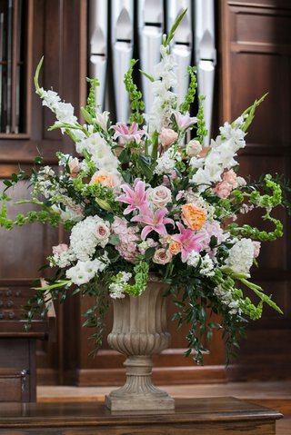 a-bright-floral-arrangement-with-white-pink-and-orange-flowers-in-church