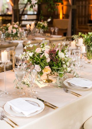 long-reception-table-with-crystal-candleholder-low-centerpiece-gold-vessel-with-green-leaves-pink